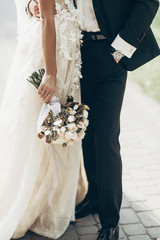 Fototapeta luxury wedding couple hugging and holding golden bouquet of roses with ribbons  in park. stylish groom and gorgeous bride in expensive gown. wedding reception. space for text. obraz