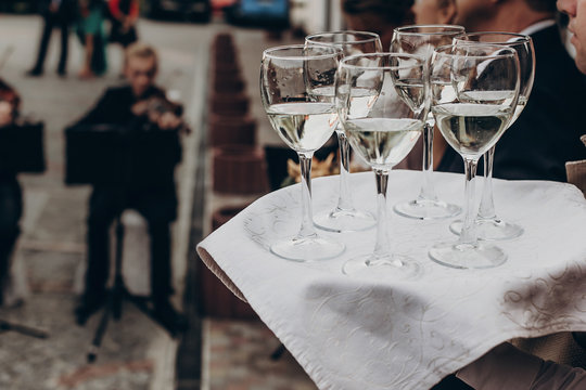 luxury life concept. glasses with champagne and wine on tray at luxury wedding reception ta restaurant.  waiter serving drinks among guests at stylish celebration. space for text