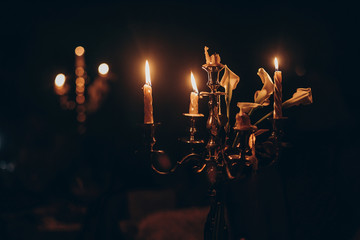candle light. candles burning on golden candlestick in church at wedding ceremony. atmospheric moment. spirituality concept . hope and sorrow. mourning