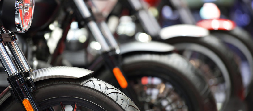 Closeup of motorcycles front wheel parked in exhibition
