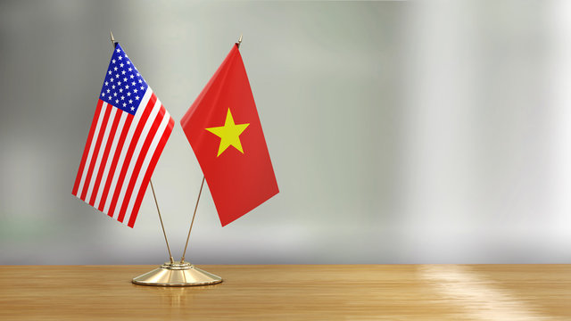 American and Vietnamese flag pair on a desk over defocused background