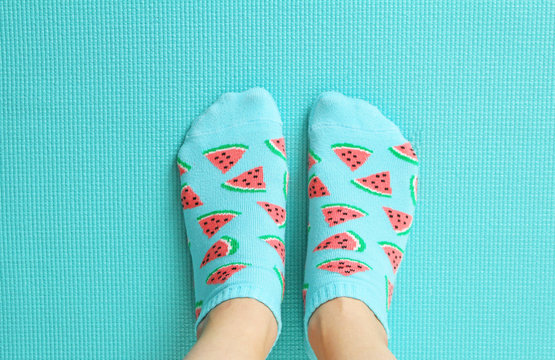 Female feet in colorful socks in watermelon print on a pastel mint background. Top view.Copy space.