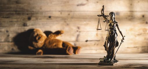 The Statue of Justice symbol with teddy bear, legal law rape concept image