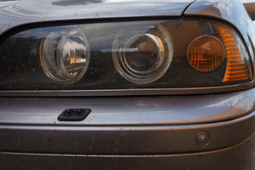 The dirty headlights of a car. Close-up