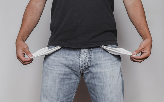 Poor man concept with adult caucausian male showing his empty pockets