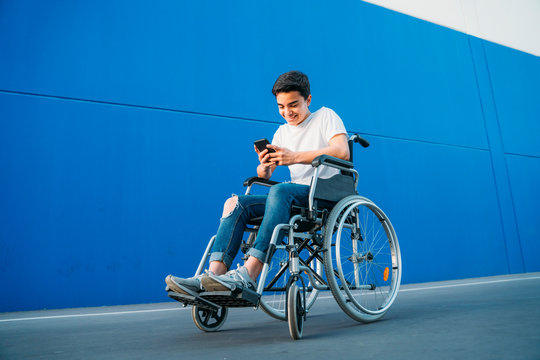 Portrait of young man on wheelchair using mobile phone