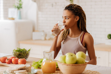 Slim and fit woman drinking water before having breakfast
