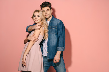 smiling girlfriend and handsome boyfriend in denim shirt hugging and looking at camera Wall mural