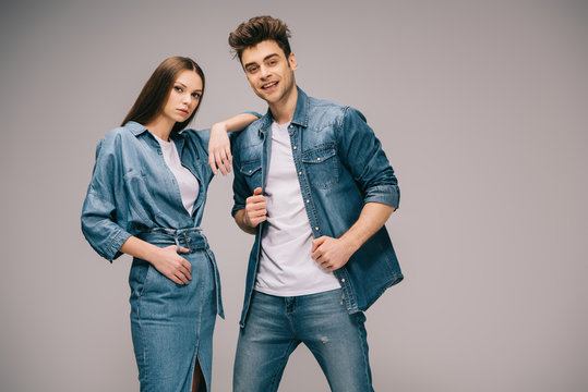 girlfriend in denim dress and smiling boyfriend in jeans and shirt looking at camera