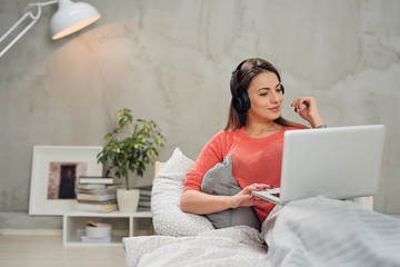 Gorgeous Caucasian  brunette listening music and using laptop while sitting on the bed in bedroom.