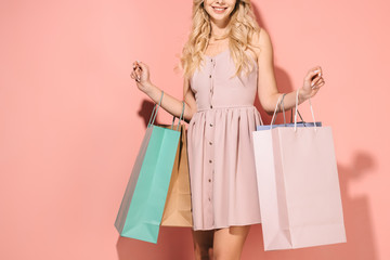 partial view of blonde woman holding shopping bags on pink background