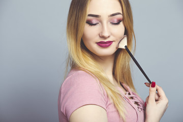 Wall Mural - portrait of a beautiful young girl with makeup brush in a studio, woman face, cosmetics and natural beauty concept