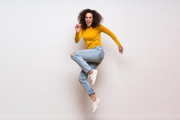 Obraz Dominican woman with curly hair jumping over isolated white background - fototapety do salonu