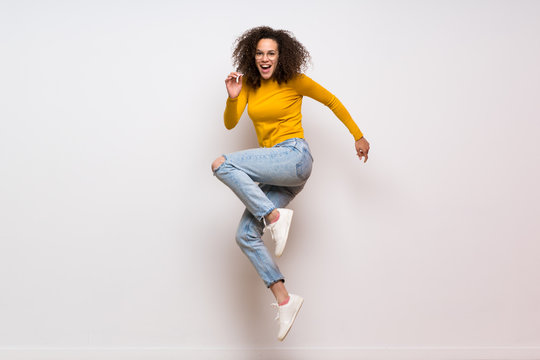 Dominican woman with curly hair jumping over isolated white background