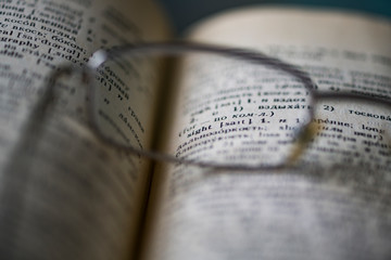 """Points are on the page of the English-Russian dictionary. Through the lens points you can see the word """"sight"""". Concept: glasses help with vision problems. Selective focus. Blurred image."""