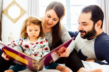 A mother father and child daughter reading book in bed before going to sleep
