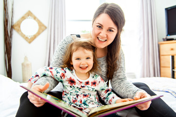 A mother and child daughter reading book in bed before going to sleep