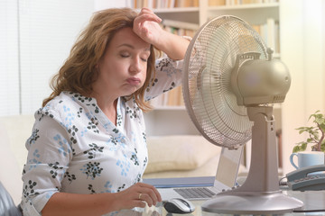 Woman suffers from heat in the office or at home Wall mural