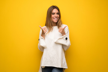 Blonde woman over yellow wall giving a thumbs up gesture with both hands and smiling