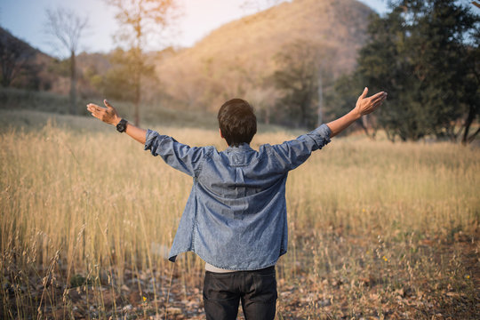 Summer, freedom and holidays concept.Happy man raised arms and enjoying in the nature. Young cheering man open arms at sunrise.