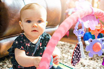 A cute baby playing with colorful toy at home