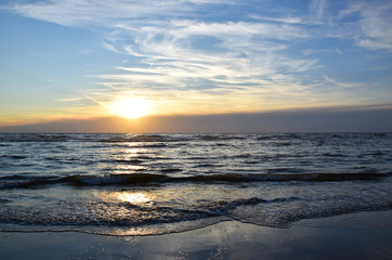 Sunset over the Ocean - View of the red sun sinking into the horizon and waves washing over the sand of the beach