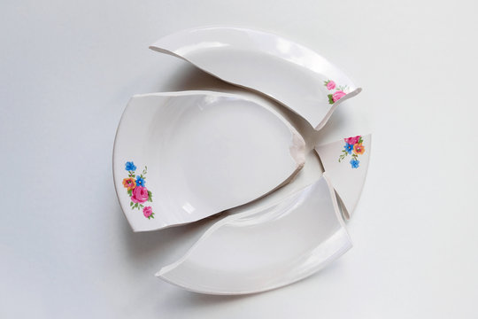 broken white plate with flowers pattern on white background