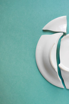 broken white plate on green background, copy space, vertical top view