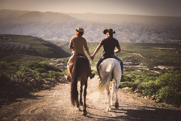 Romantic couple wide horses together holding hands with love and romance in outdoor leisure lifestyle alternative activity - viewed from back young people with aninmals Wall mural