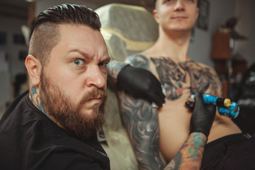 Bearded professional tattoo artist making angry face to the camera, while working with his male client, tattooing him on chest. Tattooist making funny face while working