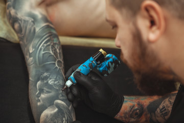 Cropped close up rear view shot of a bearded tattooist working at his studio, tattoing arm of his client. Professional tattoo artist using tattooing machine at work, copy space