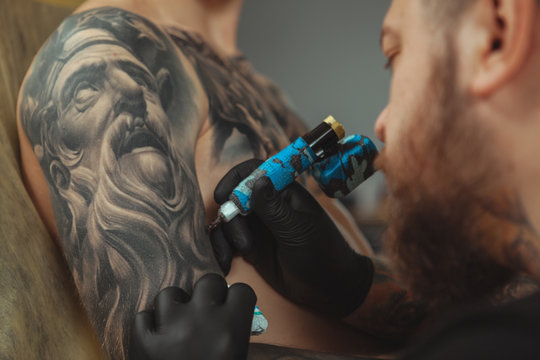 Cropped close up of a bearded tattoo artist working at his studio tattooing sleeve on the arm of his male client. Man getting tattooed by professional tattooist