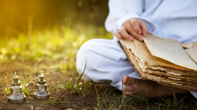 Buddhist  monk sits in  yoga lotus position meditating, reading old open book of wisdom, and there are a number  Tibetan bells and burn incense at meadow. beautiful sunset background