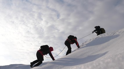 three Alpenists in winter climb rope on mountain. Travelers climb rope to their victory through snow uphill in strong wind. tourists in winter work together as team overcoming difficulties. Wall mural