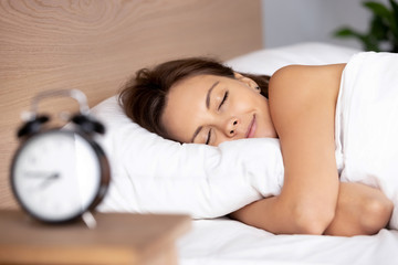 Pretty female sleeping on bed alarm clock on bedside table