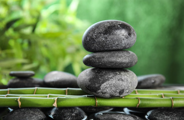 Zen stones on bamboo against blurred background