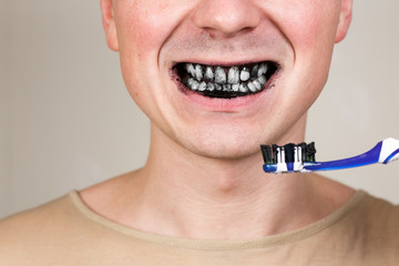 young man holding tooth brush with black active charcoal toothpaste