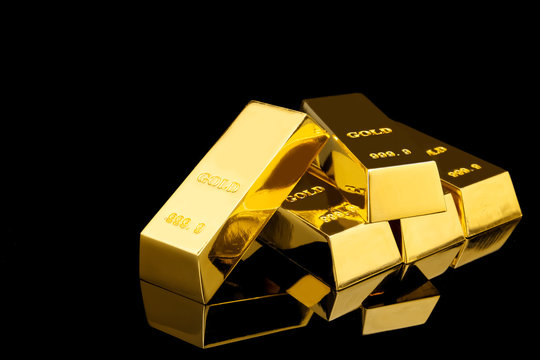 Shiny gold bars on black background. Space for text