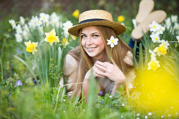 Portrait a beautiful woman in straw hat with  daffodils flowers in the garden. Gardening.