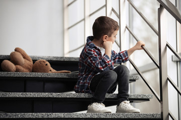 Sad little boy with toy sitting on stairs indoors Wall mural