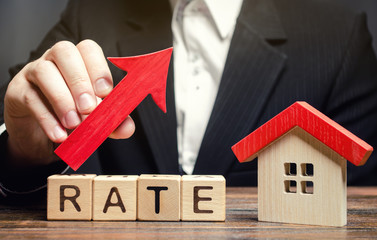 A man holds a red arrow up above the word Rate and a wooden house. The concept of raising interest rates on mortgages. The increase in property tax rates. Real estate capitalization. Insurance. Fototapete