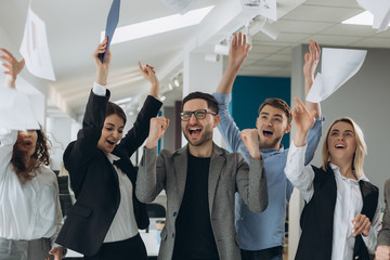 Group of business people celebrating by throwing their business papers and documents fly in air, Power of cooperation, Success teamwork concept