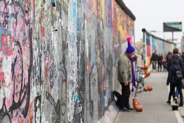 Close-up of graffiti at the East Side Gallery, section of the Berlin Wall in Berlin, Germany. Street musician and tourists in the background.