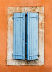 Fototapeta stara niebieska drewniana okiennica na pomarańczowej ścianie - Roussillon, Prowansja, Francja obraz