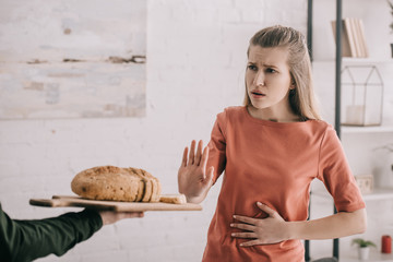 cropped view of man holding cutting board with bread near upset blonde woman with gluten allergy