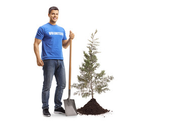 Young male volunteer with a shovel standing next to a tree and soil