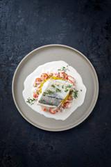 Gebratenes Schellfisch Filet mit Safran Reis und Krabben in Krebs Sauce als Draufsicht auf einem Modern Design Teller