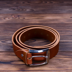 Ginger color handmade belt lies on textured wooden background. The belt is twisted into a ring. Closeup side view. Stock photo of businessman accessories.