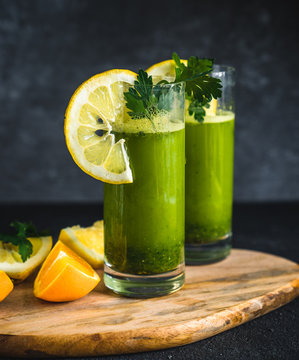 Fresh green juice made from parsley, oranges and lemons. Green smoothie with parsley on black background.