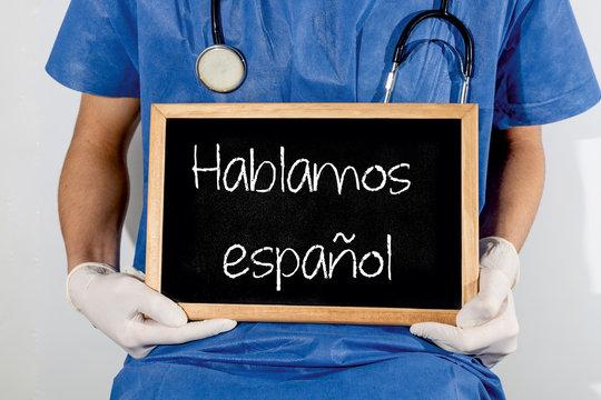 Doctor shows information on blackboard: we speak spanish.  Medical concept.